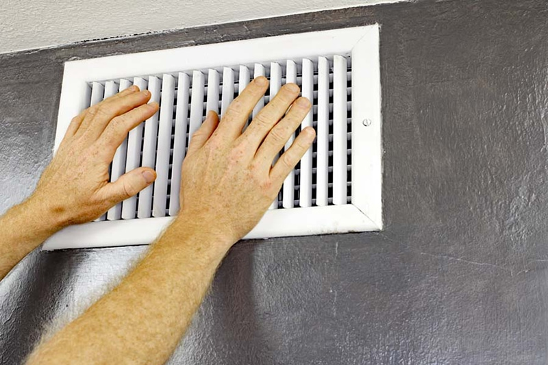 Why Is My AC Blowing Hot Air? A pair of adult male hands feeling the flow of air coming out of an air vent on a wall near a ceiling. Man with hands in front of an air vent feeling for air flow.